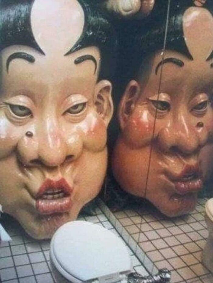 """Situado en un bar en Shinjuku, Japón. Hay un cuarto de baño con una cabeza pintada situada delante del retrete. Activada por la presión del asiento, la cara canta una extraña melodía de borrachera y se mueve lentamente hacia ti... haciendo la habitación cada vez más pequeña, hasta que sus labios te """"besan"""" las rodillas"""