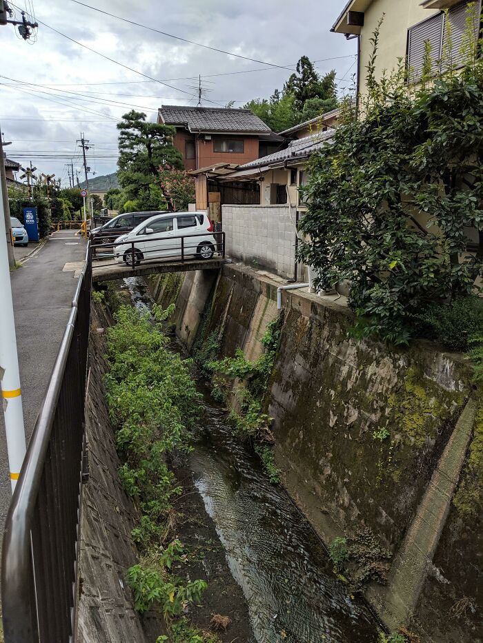 Car Is Parked In The Driveway Which Is Built Over A Small Stream In Kyoto, Japan