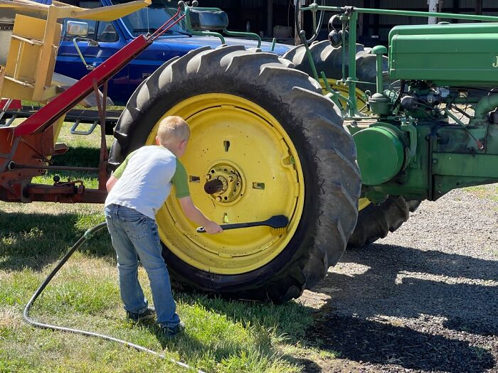 Our Grandson Cleaning Tractor Tires As We Begin Baling Hay.