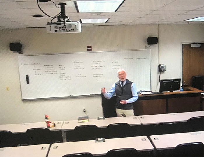 My Professor Is 74 And He Isn't Confident Using Zoom So He's Prerecorded The Rest Of Our Classes. Today, I Watched The First One. He Has A Pinocchio Doll In The Front Row Because He Isn't Comfortable Teaching To An Empty Room. I'm Social Distancing For This Man And This Man Only
