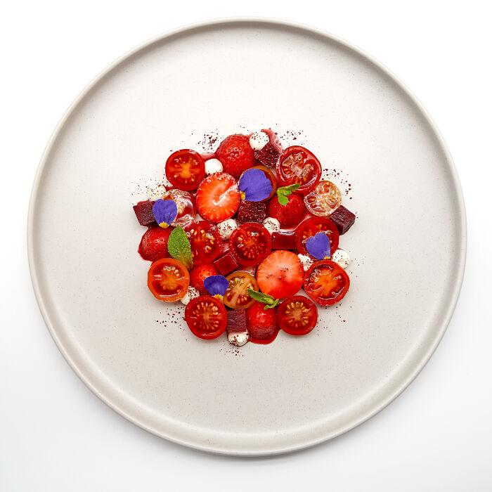 Ensalada de tomates cereza y frutillas, con mousse de queso de cabra, remolacha, menta, y zumaques