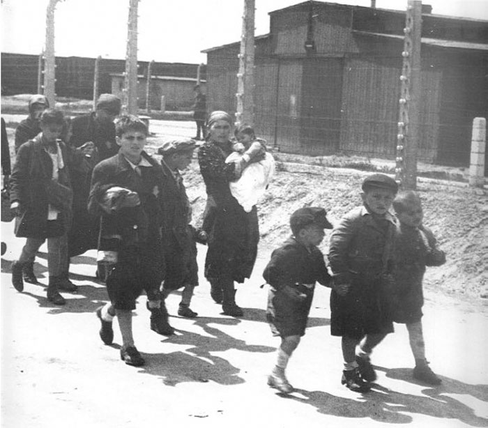 Niños judíos cogidos de la mano mientras caminan sin saberlo hacia su muerte en las cámaras de gas de Auschwitz