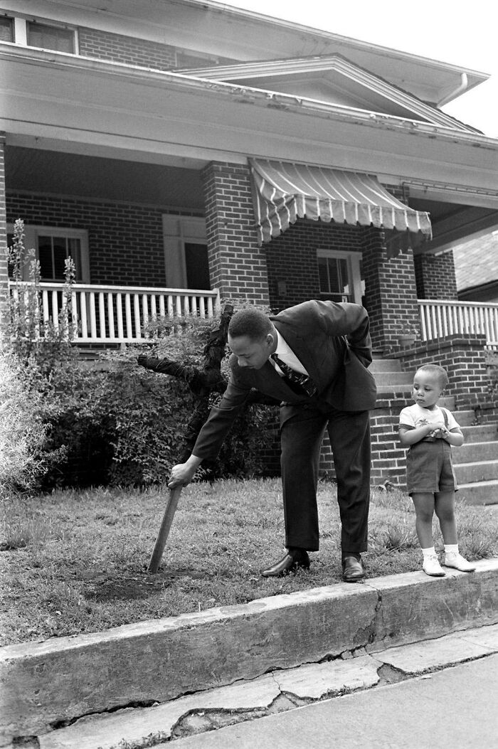Martin Luther King Jr. With His Son, Pulling Up A Burnt Cross From The Front Lawn Of His Atlanta Home, April 1960