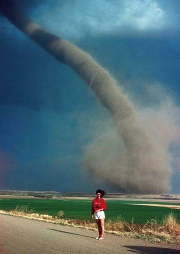 Una chica posa junto a un tornado de categoría F1 a 1,6 km de distancia