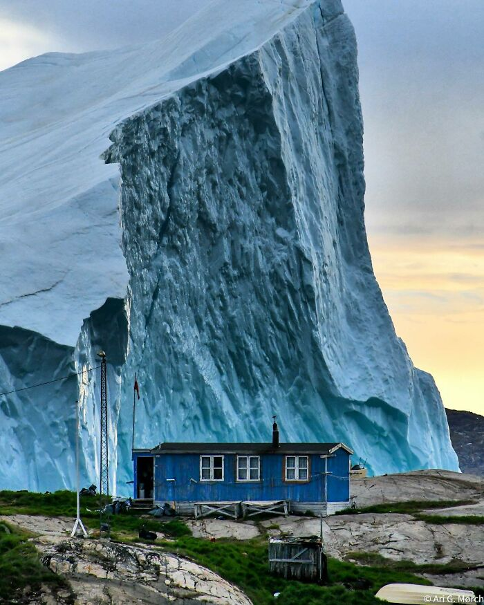 Iceberg Passing A House In Greenland