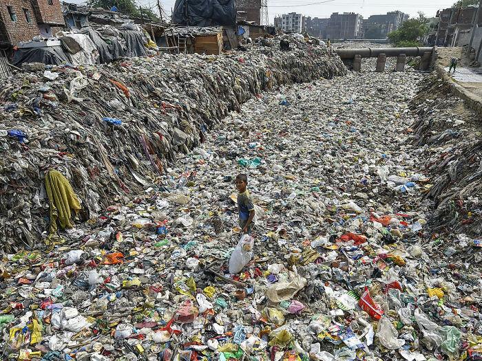 Un niño recoge artículos reciclables de un desagüe semiseco, en Taimoor Nagar, Nueva Delhi