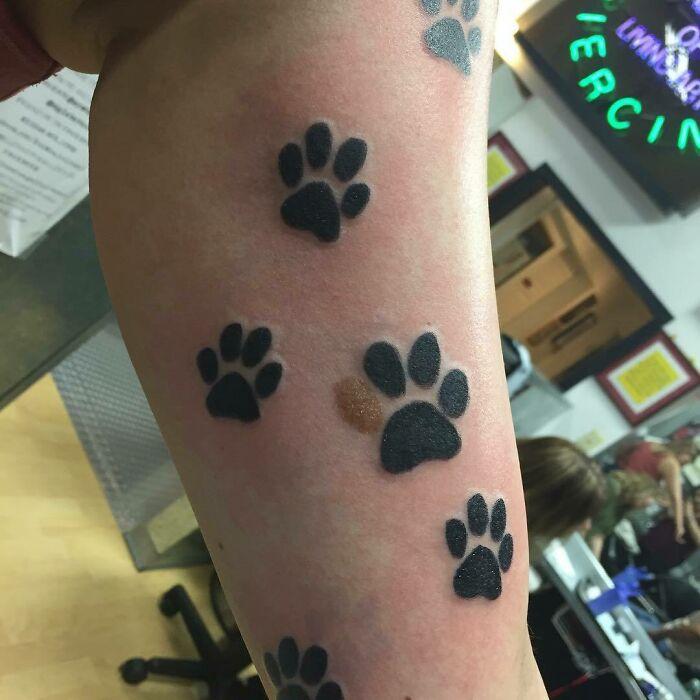 Tatuaje con forma de pata alrededor de una marca de nacimiento