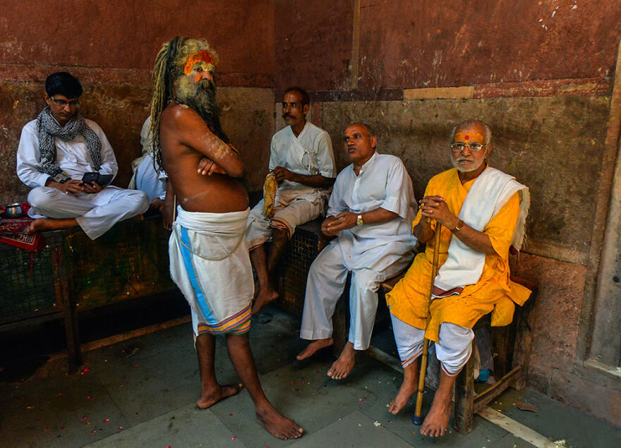 A Priest And Locals Sit Around By Robi Chakraborty