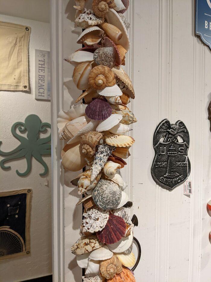 Cerca de 2.4 metros de largo, colgando de un marco de puerta. Varias conchas marinas hermosas atadas a una cuerda central. Los ángulos, las texturas, y lo apretado que están ensartadas nunca permitiría que un plumero pase correctamente. El cordón central es de cáñamo, así que no se puede mojar. Y las pequeñas grietas son imposibles de alcanzar, especialmente en la espiral y las conchas huecas. Hermosa idea, pero el imán de polvo que es me hace querer quemarlo con fuego